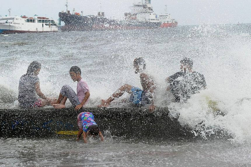 Residents along Manila Bay play in the waves created by nearby Typhoon Noul on May 10, 2015, as it approaches the northern Philippines. -- PHOTO: AFP