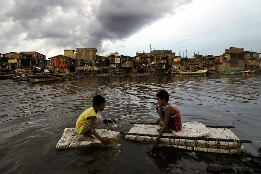 Young Filipinos paddle next to secured boats awaiting the arrival of typhoon Noul in Navotas city, north of Manila, Philippines, on May 10, 2015. -- PHOTO: EPA