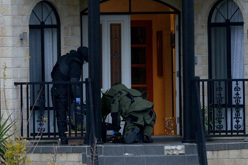 """Officers wearing bomb suits raid a home in Greenvale, Melbourne, Australia, on May 8, 2015. An Australian teenager, who was arrested during the raid, has been charged with involvement in a """"well advanced terrorist bomb plot and was remanded in custod"""