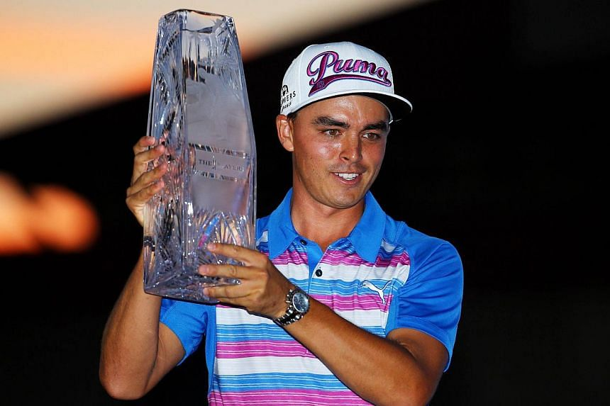 Rickie Fowler celebrates with the winner's trophy after the final round of The Players Championship at the TPC Sawgrass Stadium course on May 10, 2015 in Ponte Vedra Beach, Florida. -- PHOTO: AFP
