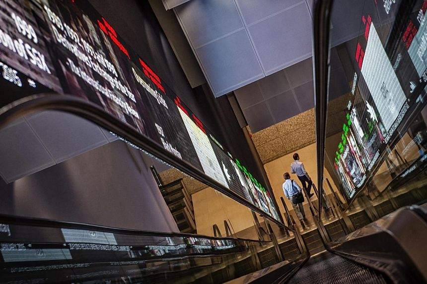 Pedestrians exiting an escalator that runs past an electronic screen and ticker board indicating stock figures at the Singapore Exchange Ltd. (SGX) headquarters in Singapore on Jan 21, 2015. -- PHOTO: BLOOMBERG
