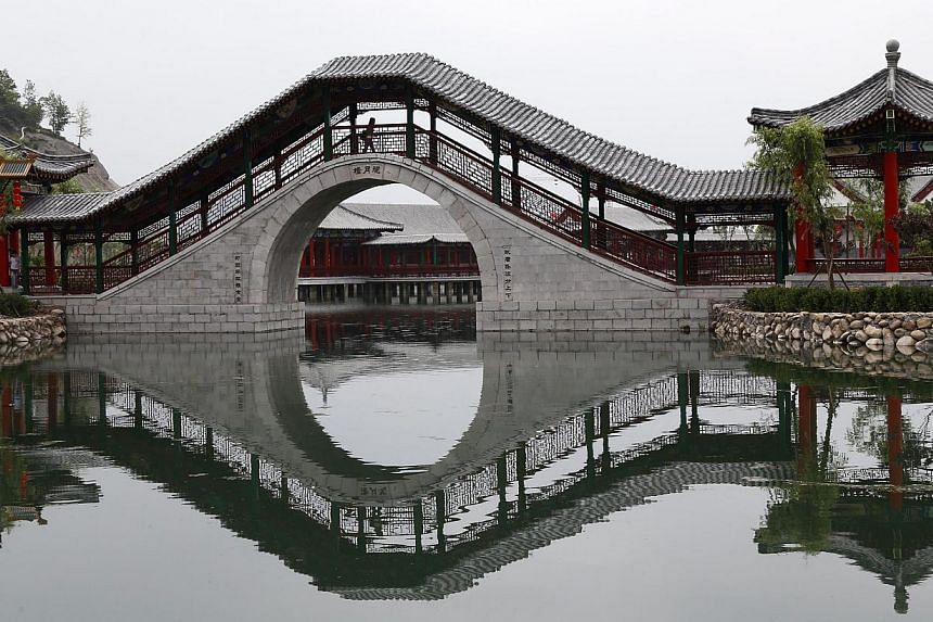 A tourist walks across a bridge of a scenic area which is part of a replica of Beijing's Old Summer Palace or Yuanmingyuan, built in Hengdian town of Zhejiang province, eastern China on May 10, 2015. -- PHOTO: EPA