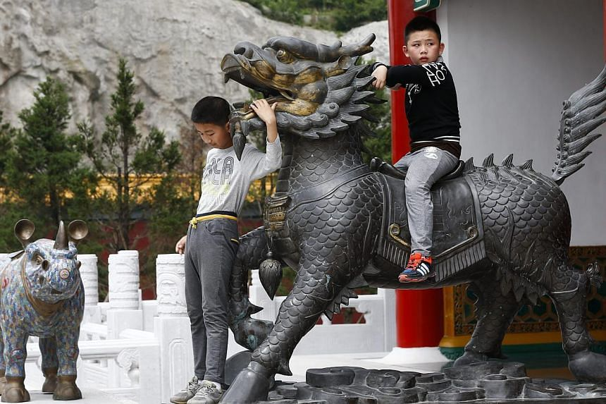 Young tourists climb an outdoor display of a scenic area which is part of a replica of Beijing's Old Summer Palace or Yuanmingyuan, built in Hengdian town of Zhejiang province, eastern China on May 10, 2015. -- PHOTO: EPA