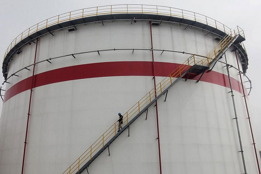 A worker walks down the stairs of an oil tank at a refinery in Wuhan, Hubei province on March 23, 2012. China overtook the United States as the world's top importer of crude oil for the first time in April, and its purchases are expected to remain st