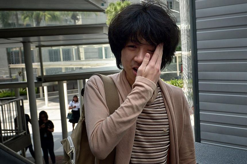 Amos Yee holding his face in pain after a man slapped him hard on the left cheek, as he was walking alone to the State Courts on April 30, 2015.  -- ST PHOTO: KUA CHEE SIONG