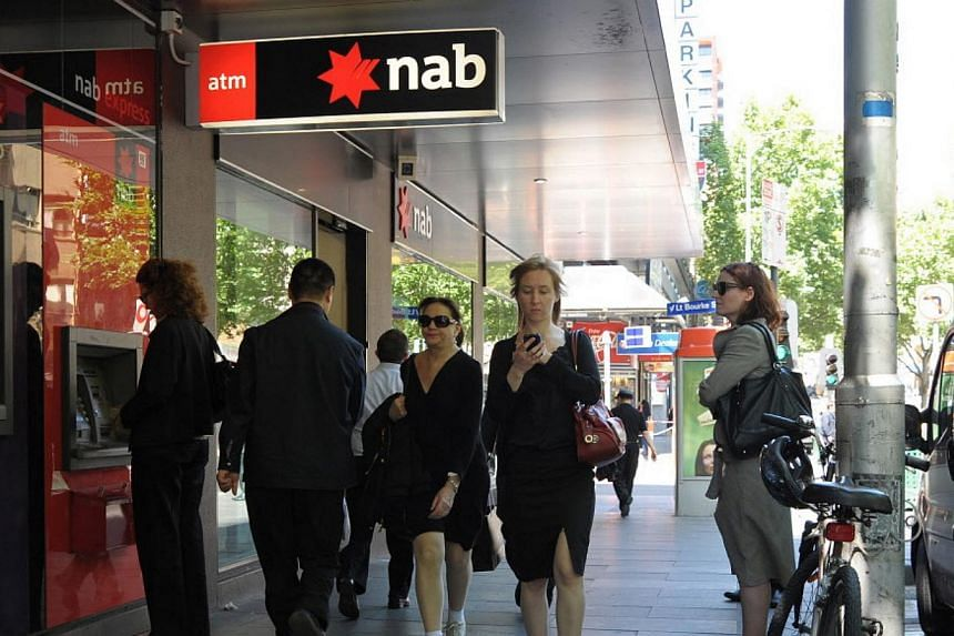 People walking past and queueing at the National Australia Bank (NAB) ATM machine. -- PHOTO: BLOOMBERG