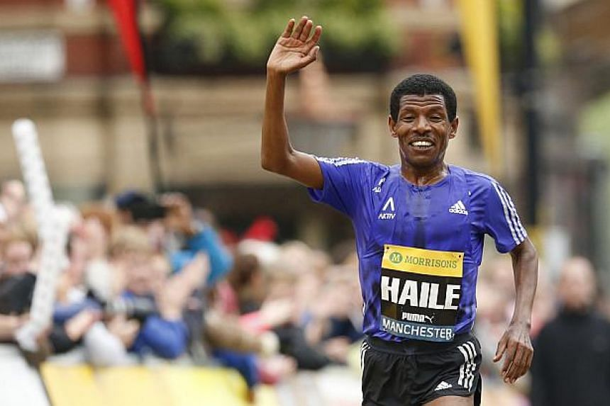 Ethiopia's Haile Gebrselassie waves as he approaches the finish line at the end of the Morrisons Great Manchester Run. During an interview afterwards, he announced his retirement. -- PHOTO: REUTERS