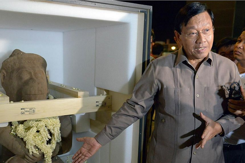 Cambodian secretary of state of council of ministers Chan Tany talks to media alongside a 10th-century statue of the Hindu monkey god Hanuman upon its arrival at Phnom Penh International Airport on May 10, 2015. TheCleveland Museum of Art