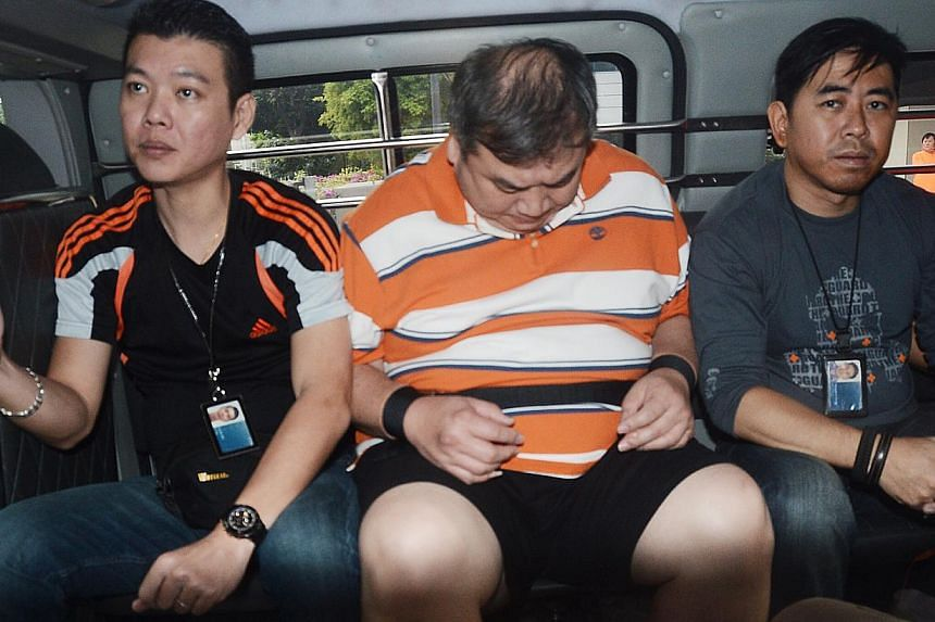 Heng Chen Boon (centre), a credit card promoter, in the police van on Jan 17, 2014. Heng has been charged for the kidnapping of Madam Ng Lye Poh, the mother of Sheng Siong supermarket boss Lim Hock Chee. -- PHOTO: SHIN MIN