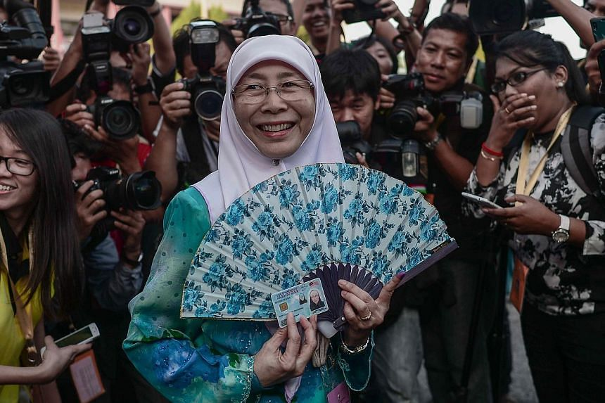 Parti Keadilan Rakyat (PKR) president Wan Azizah Wan Ismail (centre), wife of Malaysian opposition leader Anwar Ibrahim, arrives at a polling station during a by-election in Permatang Pauh, in the northern Malaysian state of Penang on March