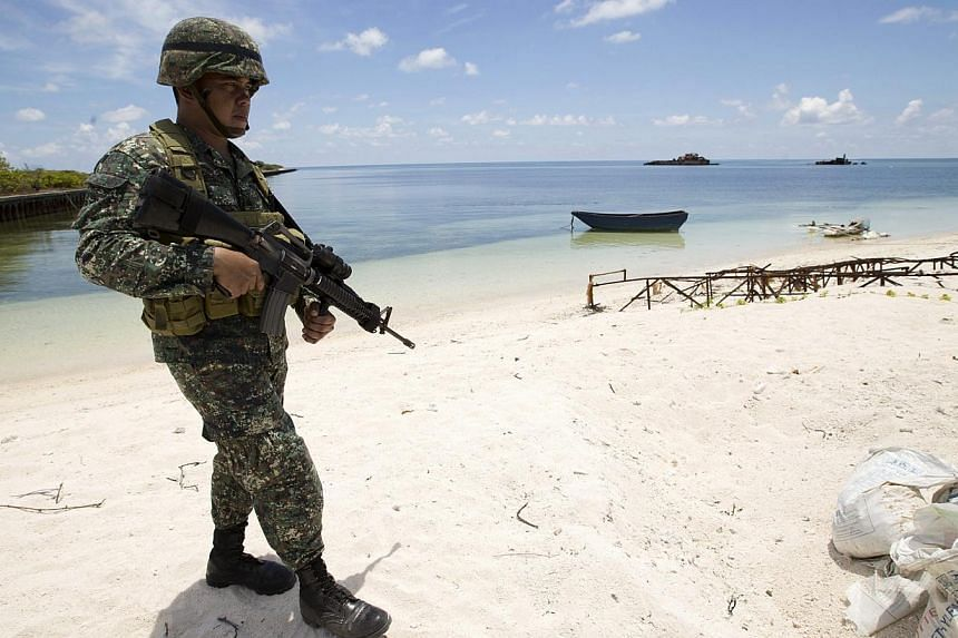 A Filipino soldier patrols at the shore of Pagasa island (Thitu Island) in the Spratly group of islands in the South China Sea, west of Palawan, Philippines on May 11, 2015. -- PHOTO: EPA