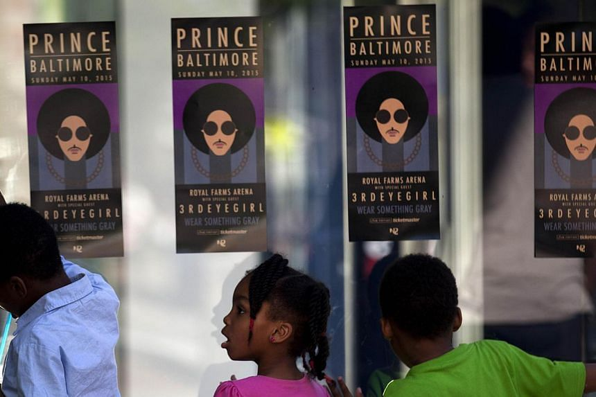 """Children look through the glass as fans of musical artist Prince enter a """"Rally 4 Peace"""" concert in Baltimore, Maryland on May 10, 2015. -- PHOTO: AFP"""