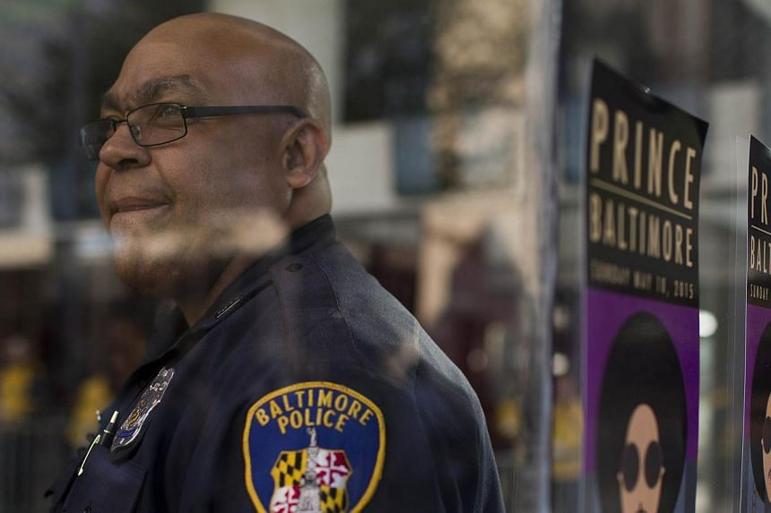 """A police officer at a """"Rally 4 Peace"""" concert by Prince looks on in Baltimore, Maryland on May 10, 2015. -- PHOTO: AFP"""