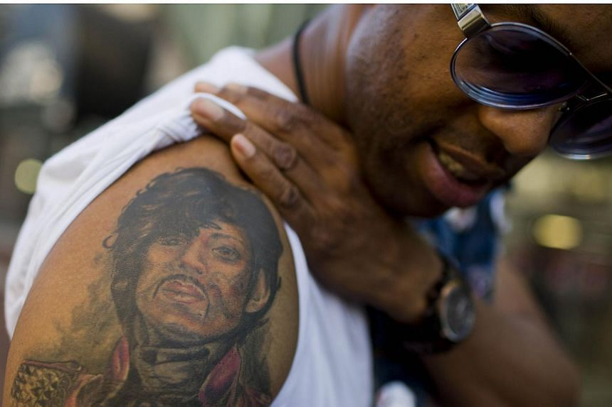 """Prince fan Ash poses with his Prince tattoo before entering a """"Rally 4 Peace"""" concert in Baltimore, Maryland on May 10, 2015. -- PHOTO: AFP"""
