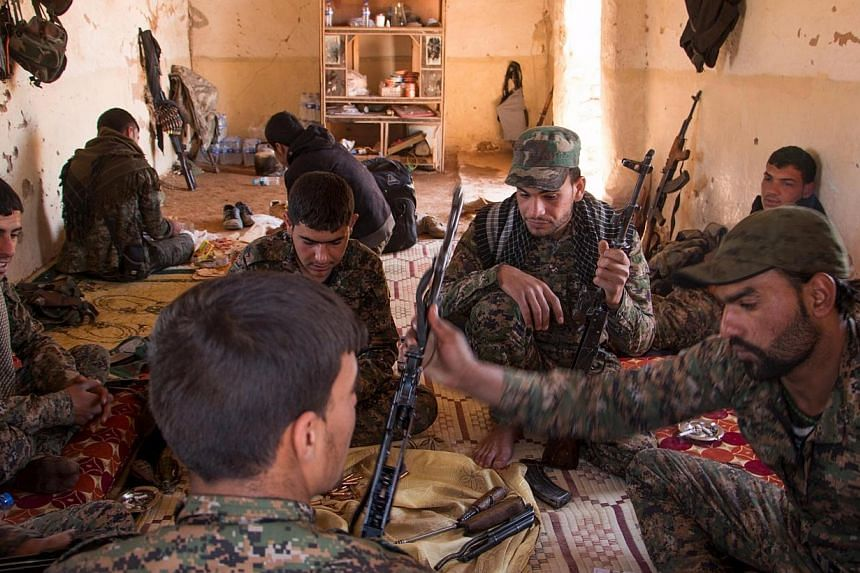 Kurdish People's Protection Units (YPG) fighters clean their weapons inside a safehouse after what they said were clashes with ISIS fighters in the southern countryside of Ras al-Ain on May 8. -- PHOTO: REUTERS