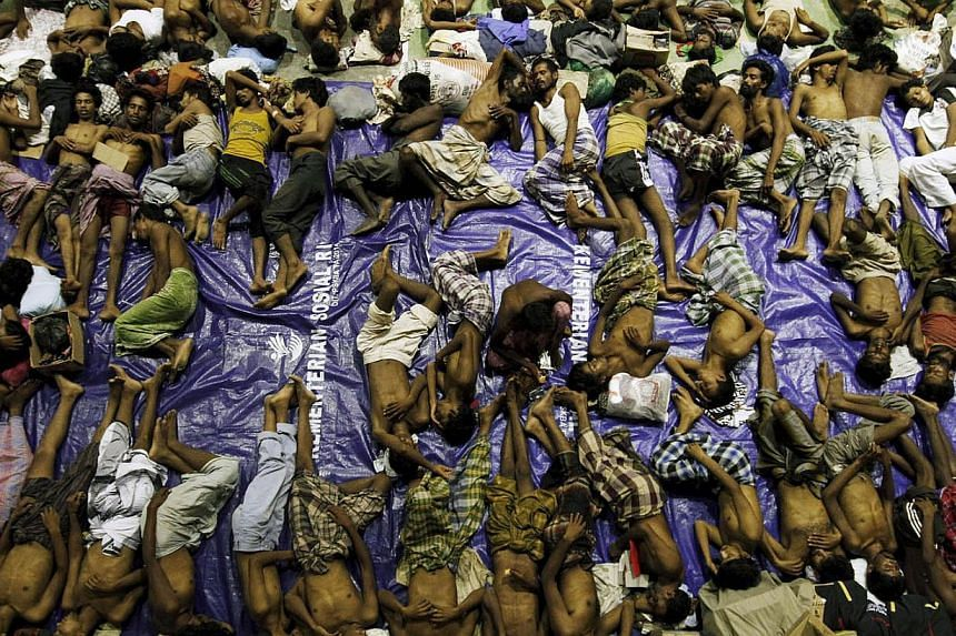 Migrants believed to be Rohingya rest inside a shelter after being rescued from boats at Lhoksukon in Indonesia's Aceh Province May 11, 2015. -- PHOTO: REUTERS