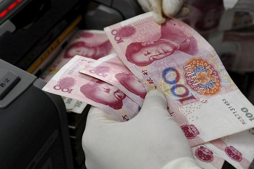 An employee counting Renminbi (RMB) banknotes at a branch of Bank of China in Changzhi, Shanxi province. -- PHOTO: REUTERS