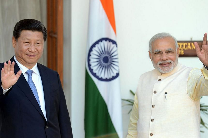 Chinese President Xi Jinping (left) and Indian Prime Minister Narendra Modi waving before delegation talks in New Delhi, in this Sept 18, 2014 photo. Mr Modi will take his global investment push to China this week, as Asia's rival superpowers look to