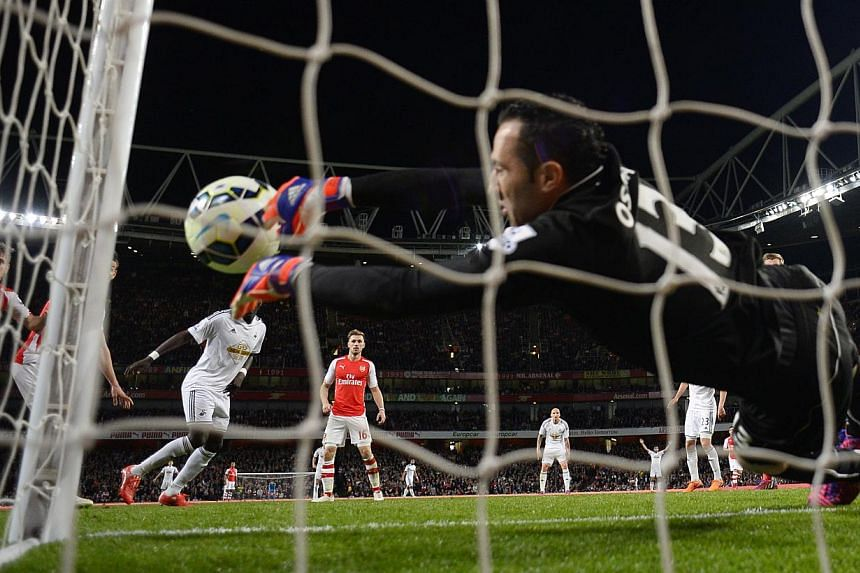 Bafetimbi Gomis scored a late, technology-assisted winner as Swansea City compromised Arsenal's quest for automatic Champions League qualification with a smash-and-grab 1-0 away victory on Monday. -- PHOTO: REUTERS