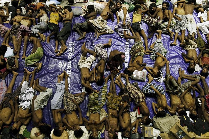Migrants believed to be Rohingya resting inside a shelter after being rescued from boats at Lhoksukon in Indonesia's Aceh Province on May 11, 2015. -- PHOTO: RETUERS