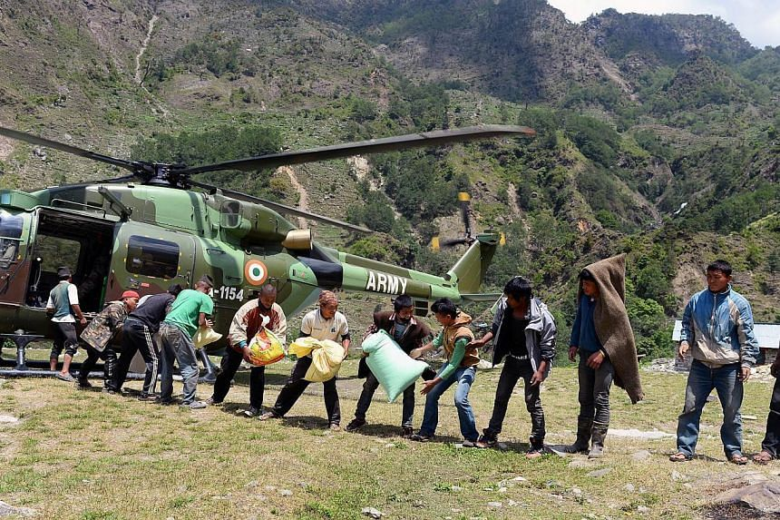 Nepalese villagers receiving relief materials from an Indian army helicopter at Bhogteni village in Gorkha on May 4, 2015. -- PHOTO: AFP
