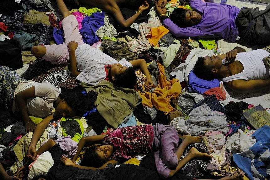 A group of rescued migrants from Myanmar and Bangladesh sleeping at a government sports auditorium in Lhoksukon, Aceh province, on May 12, 2015, after Indonesian rescuers found their boat carrying 573 passenger stranded in waters off north Aceh provi