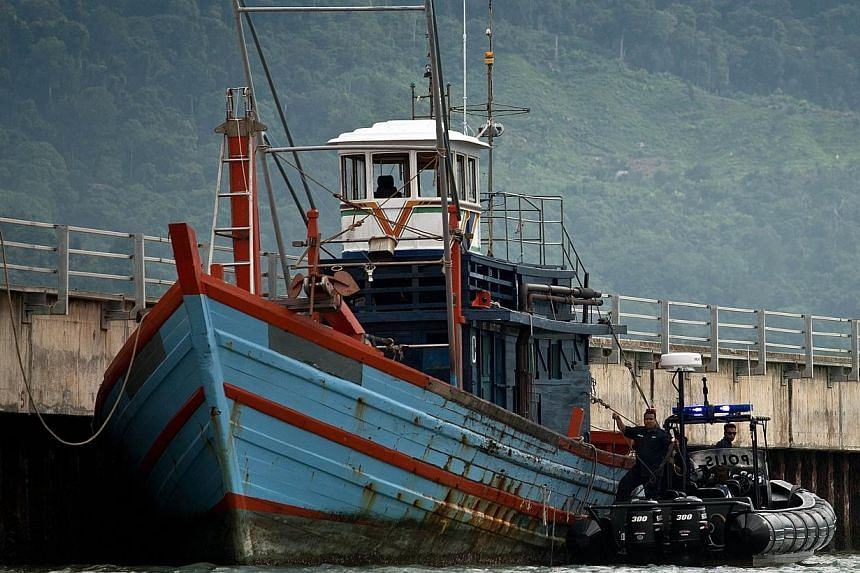 Malaysian Maritime police inspect one of the boats which carried illegal migrants in Langkawi on May 12, 2015. -- PHOTO: AFP