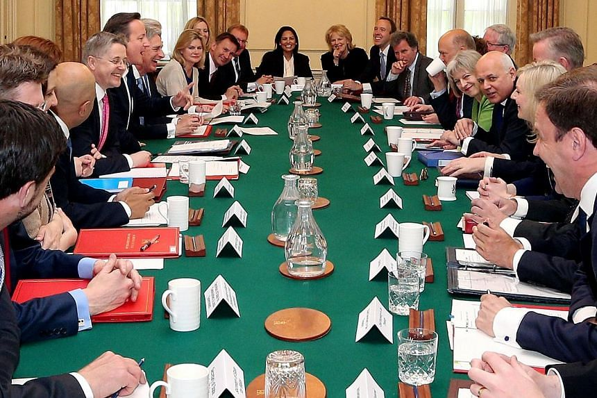 British Prime Minister David Cameron (seventh left) hosts the first weekly Cabinet meeting in Downing Street, central London, on May 12, 2015, following the May 7 general election.Cameron will hold an early referendum on membership of the Europ