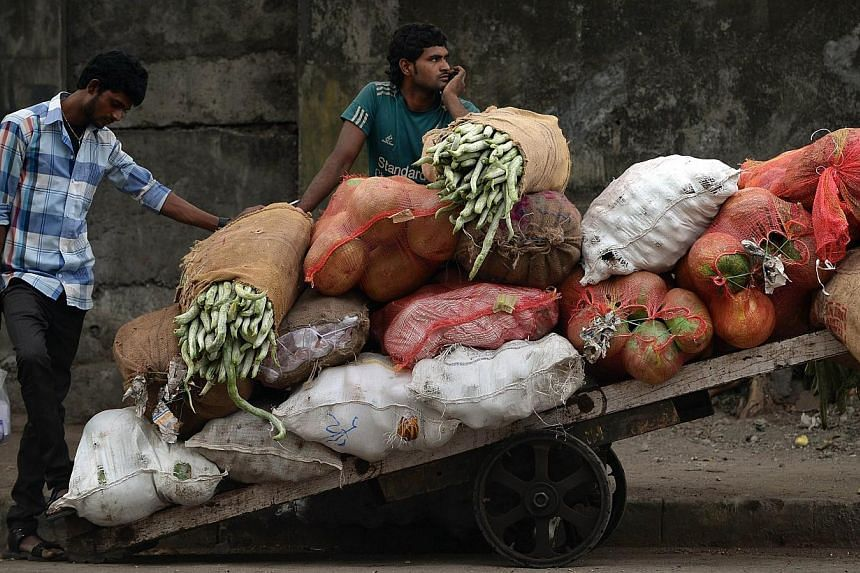 An Indian vendor waits alonside his cart filled with vegetables at the wholesale market in Mumbai on Feb 28, 2015.India's inflation rate fell to its lowest level in four months and growth in industrial output slowed, official data showed