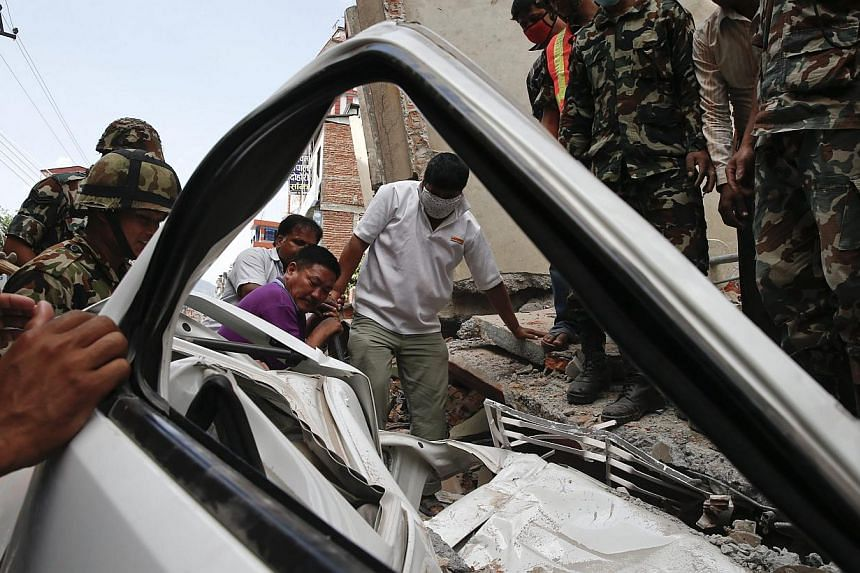 Rescue members working at a destroyed car after an earthquake in Kathmandu, Nepal, on May 12, 2015. -- PHOTO: EPA