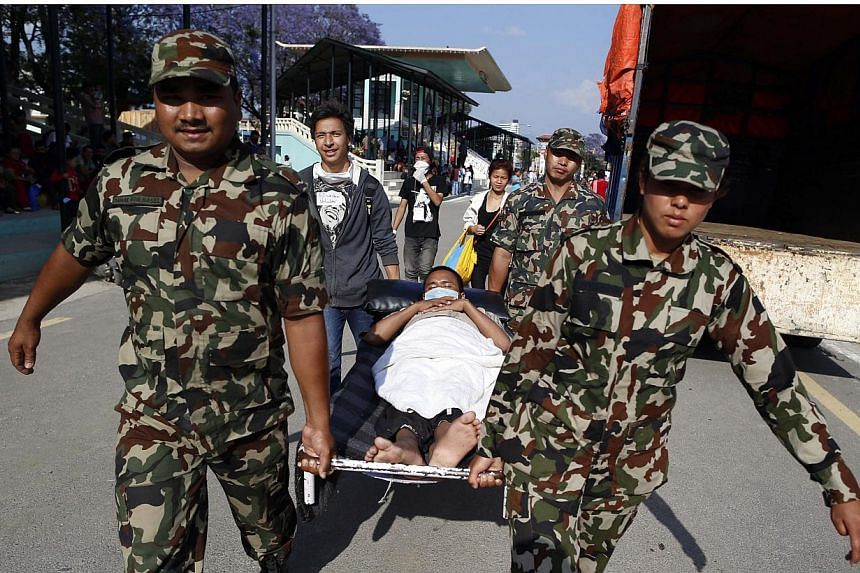 A patient is carried by Nepalese military personnel and volunteers back to the hospital building after he had been evacuated when an earthquake hit, in Kathmandu, Nepal, on May 12, 2015. -- PHOTO: EPA
