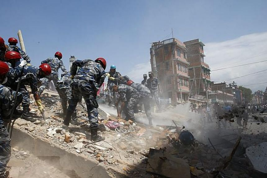 Nepalese armed police force search for victims after a house collapsed when a strong earthquake hit Kathmandu, Nepal on May 12, 2015. -- PHOTO: EPA