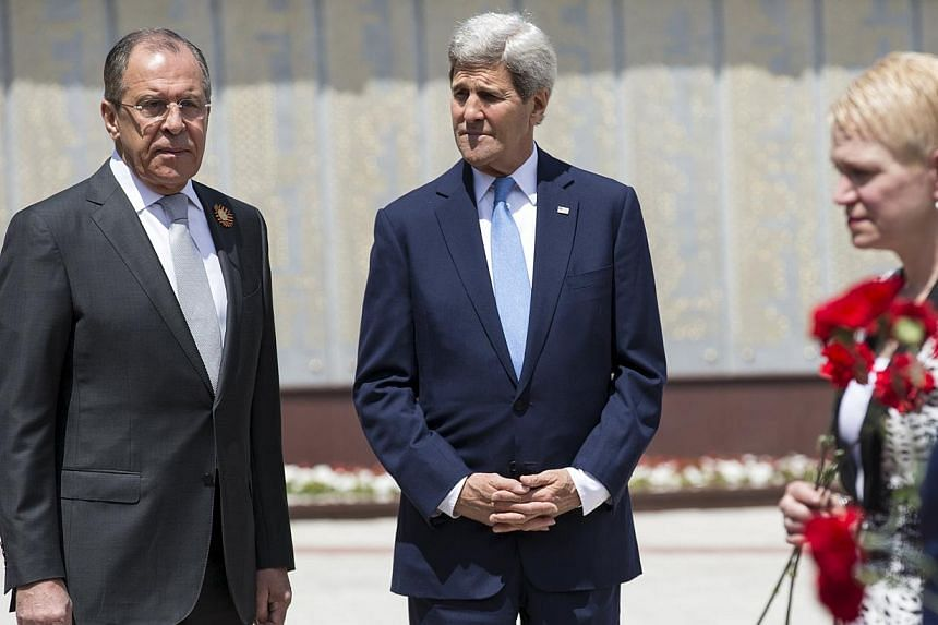 U.S. Secretary of State John Kerry (centre) and Russian Foreign Minister Sergey Lavrov watch as members of the United States and Russian delegations place red flowers at the Zakovkzalny War Memorial in Sochi, Russia May 12, 2015. -- PHOTO: REUTERS&nb