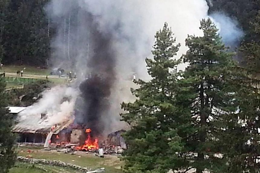 Smoke billows from the scene of the helicopter crash at Naltar in Gilgit, Pakistan on Friday that killed the ambassadors of Norway and the Philippines as well as the wives of the Indonesian and Malaysian envoys. -- PHOTO: EPA
