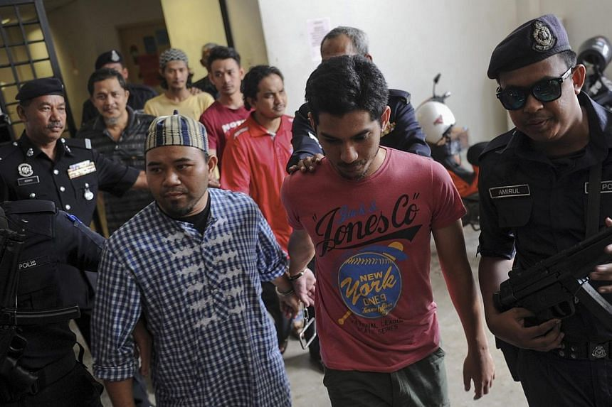 Six suspected ISIS militants (centre), including two Air Force personnel, are escorted by Malaysian Police officers outside the Sessions Court in Alor Star, Kedah, on April 30. They face up to 30 years imprisonment if convicted of promoting acts of t