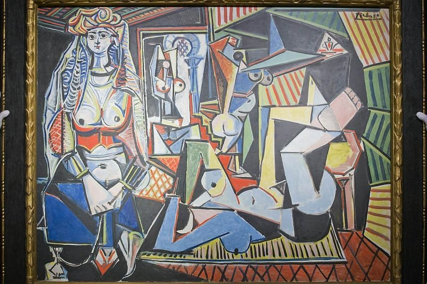 Employees of Christie's auction house hold up Spanish painter Pablo Picasso's Les femmes d'Alger (Version 'O') during a press preview in London on April 10. -- PHOTO: AFP