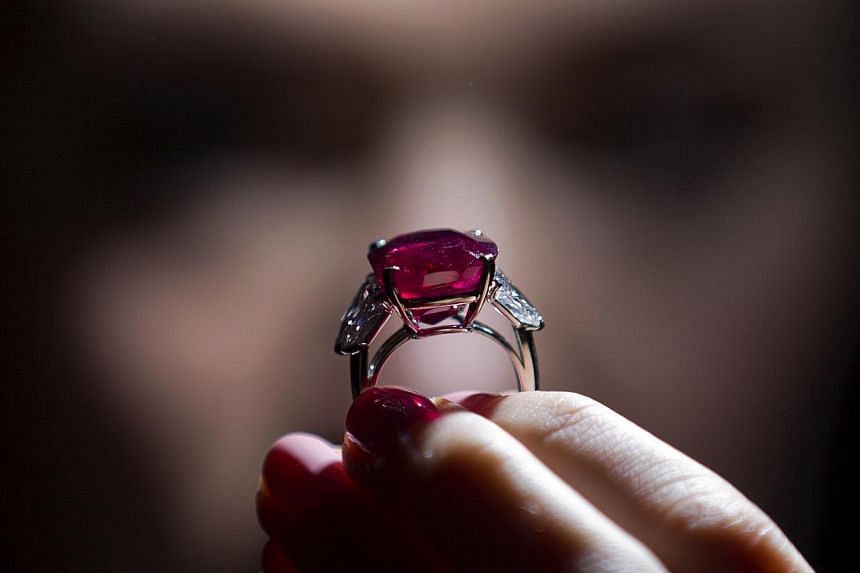 """An employee of Sotheby's auction house poses with the """"Sunrise Ruby"""", a rare Burmese ruby weighing 25.59 carats. -- PHOTO: AFP"""