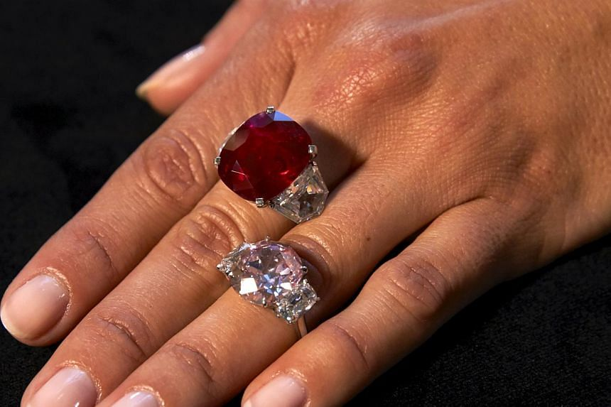 """A model showing the """"Sunrise Ruby"""" (top) and the """"Historic Pink"""" diamond during an auction preview in Geneva. -- PHOTO: REUTERS"""
