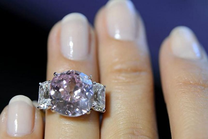 """A Sotheby's employee showing the """"Historic Pink"""", a ring with a vivid pink diamond weighing 8.72 carats and with a classic non-modified cushion cut, during a preview at Sotheby's in Geneva, Switzerland on May 6, 2015. -- PHOTO: EPA"""