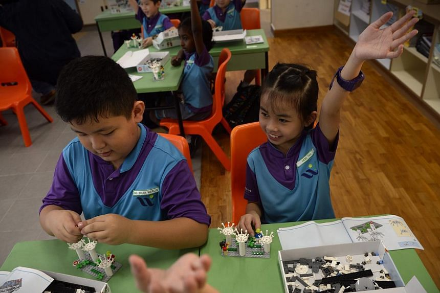 Hebe Tan, (right), a primary two student at West Spring Primary School, raising her hand during a Lego-based activity in class as her classmate Marcus Ng fixes his set on May 13, 2015. -- ST PHOTO: MARK CHEONG