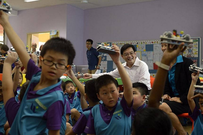 Students at West Spring Primary School holding up their Lego creations during a Lego-based activity in class during a visit by Education Minister Heng Swee Keat (centre) on May 13, 2015. -- ST PHOTO: MARK CHEONG