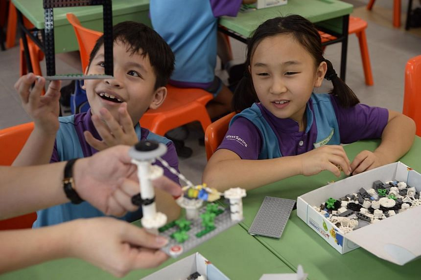 Students Brandon Tan (left) and Isabel Phan showing their Lego creations to their teacher at West Spring Primary School during a Lego-based activity in class on May 13, 2015. -- ST PHOTO: MARK CHEONG