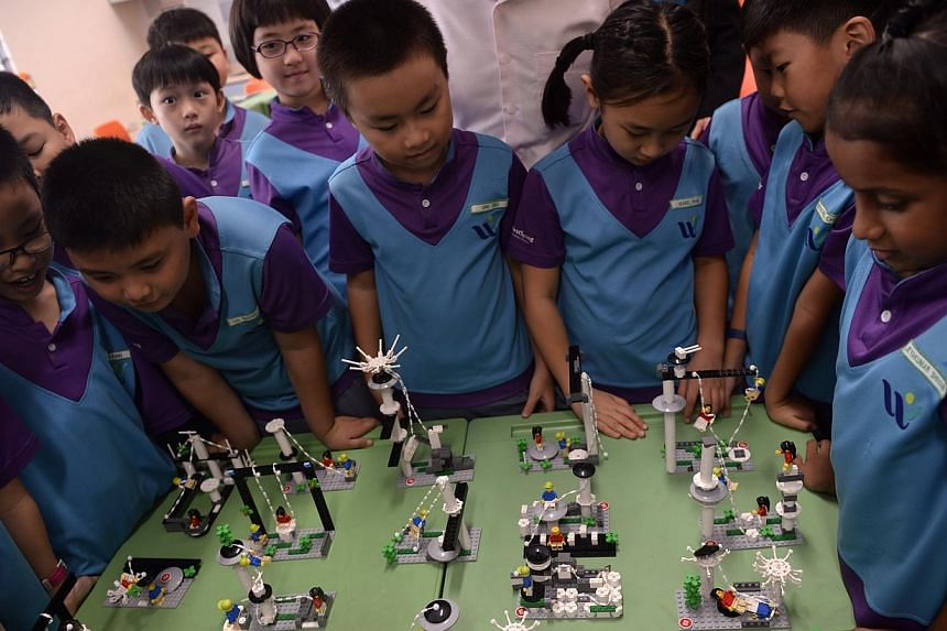 Students crowding around their Lego creations at West Spring Primary School during a Lego-based activity in class on May 13, 2015. -- ST PHOTO: MARK CHEONG