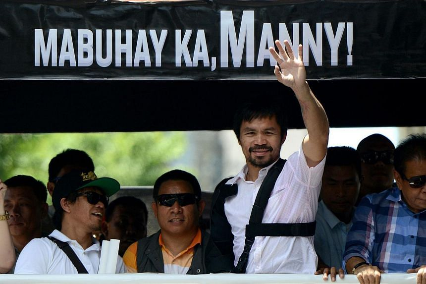 Boxing icon Manny Pacquiao (2nd right) of the Philippines waves to his supporters during a welcome parade in Manila on May 13, 2015. -- PHOTO: AFP