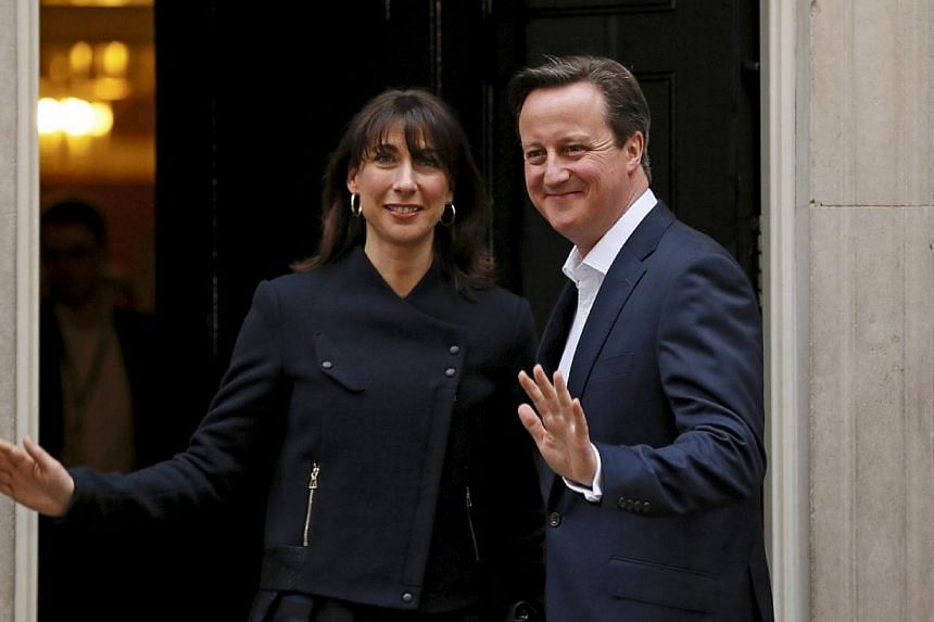 Britain's Prime Minister David Cameron and his wife Samantha wave as they arrive at Number 10 Downing Street in London, Britain on May 8, 2015. -- PHOTO: REUTERS