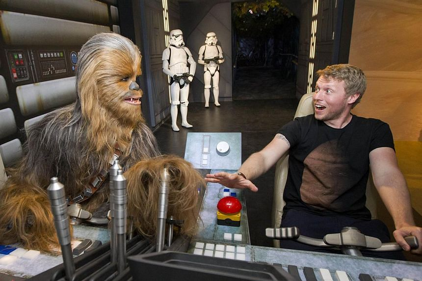 A fan poses by the wax figure of Star Wars character Chewbacca at the Star Wars At Madame Tussauds attraction in London on May 12, 2015. -- PHOTO: AFP