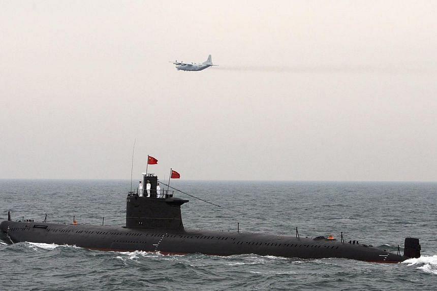 A military aircraft flies past a Chinese Navy submarine at an international fleet review to celebrate the 60th anniversary of the founding of the People's Liberation Army Navy in Qingdao, Shandong province, in this April 23, 2009 file photo. -- PHOTO