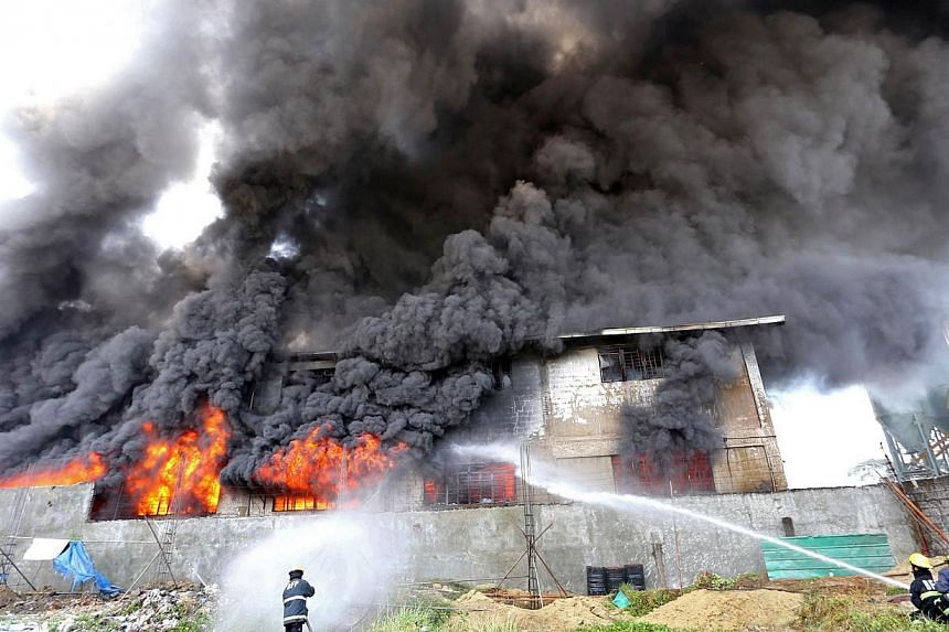 Firefighters working to put out a blaze at a plastic slipper factory in the suburb of Valenzuela in Manila, on Wednesday, May 13, 2015. The fire killed 31 workers, with dozens missing and feared dead, government and fire officials said.. -- PHOTO: AF