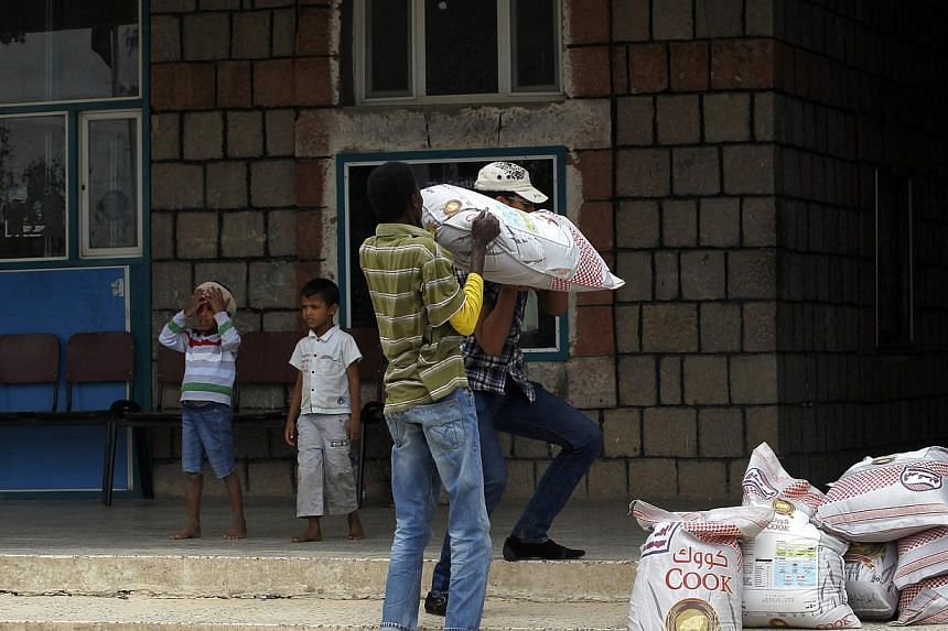 Volunteers carry aid provided for Yemenis affected by ongoing air-strikes carried out by the Saudi-led coalition inside a gymnasium turned into a temporary evacuation center in Sana'a, Yemen on May 3, 2015. A senior Iranian commander said it was Iran