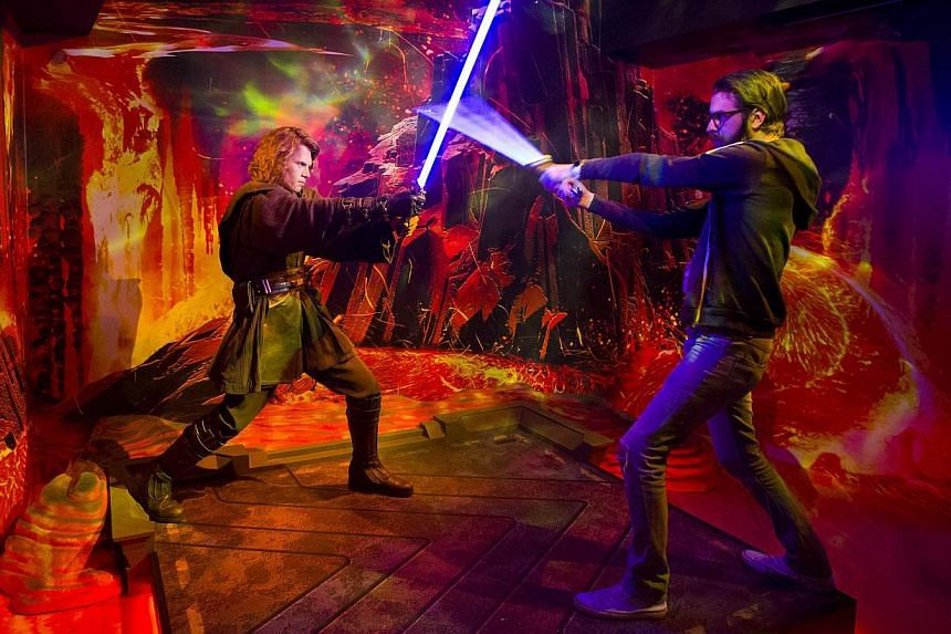 A fan battles with a wax figure of Star Wars character Annakin Skywalker on show at the Star Wars At Madame Tussauds attraction in London on May 12, 2015. -- PHOTO: AFP